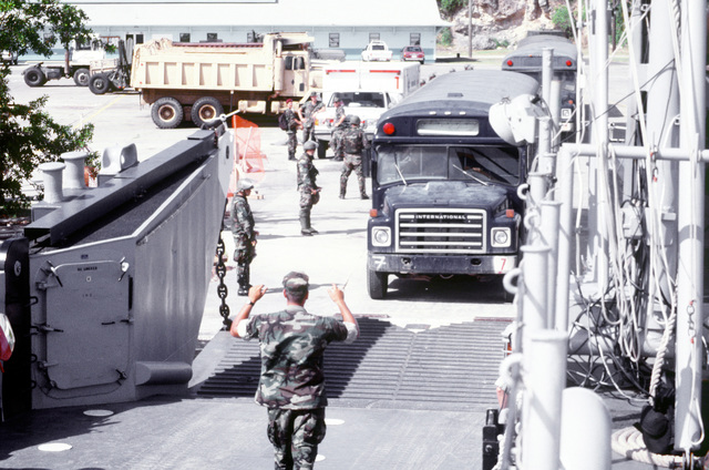 A US Air Force bus carrying Cuban immigrants drives onto a US Navy landing craft at US Naval Base Guantanamo Bay. The landing craft will transport the immigrants across Guantanamo Bay to the base's flightline