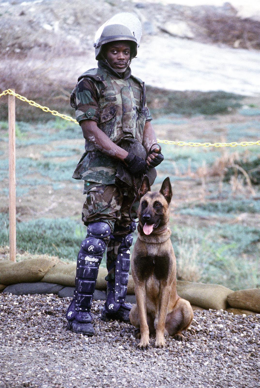 US Air Force Security Policeman AIRMAN Oswald stands with his guard dog at Camp X-ray at US Naval Base Guantanamo Bay, Cuba
