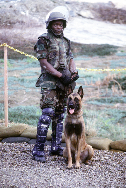 US Air Force Security Policeman AIRMAN Oswald stands with his guard dog at Camp X-ray at US Naval Base Guantanamo Bay, Cuba