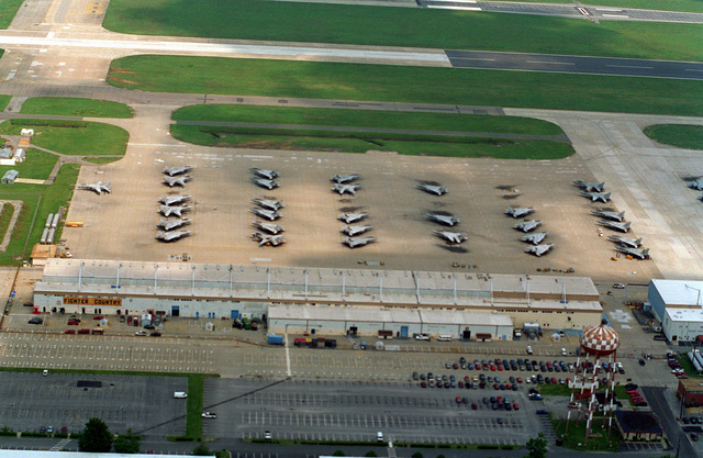 An aerial view of a section of the flight line at NAS Oceana showing F-14 Tomcat aircraft parked on the tarmac in front of the fighter country hangars