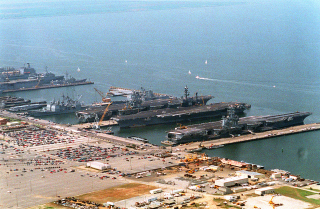An aerial view of piers 11 and 12 at the Naval Station. The three aircraft carriers are (left to right) the nuclear-powered USS DWIGHT D. EISENHOWER (CVN-69), USS AMERICA (CV-66) and the nuclear-powered USS GEORGE WASHINGTON (CVN-73)