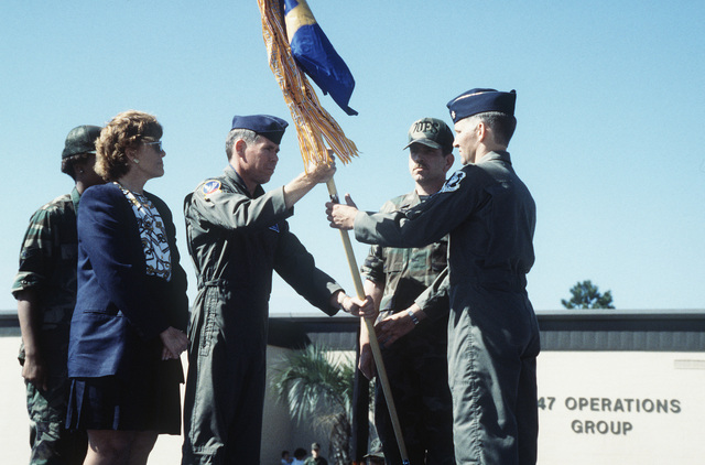 COL. John Craig, 347th Operations Group Commander, hands over the newly activated 70th OA/A-10 Thunderbolt II Attack Squadron flag to LT. COL. Lawrence Folfs as Dr. Sheila Widnall, secretary of the Air Force, looks on. Doctor Widnall participated in the activation by uncasing the unit flag