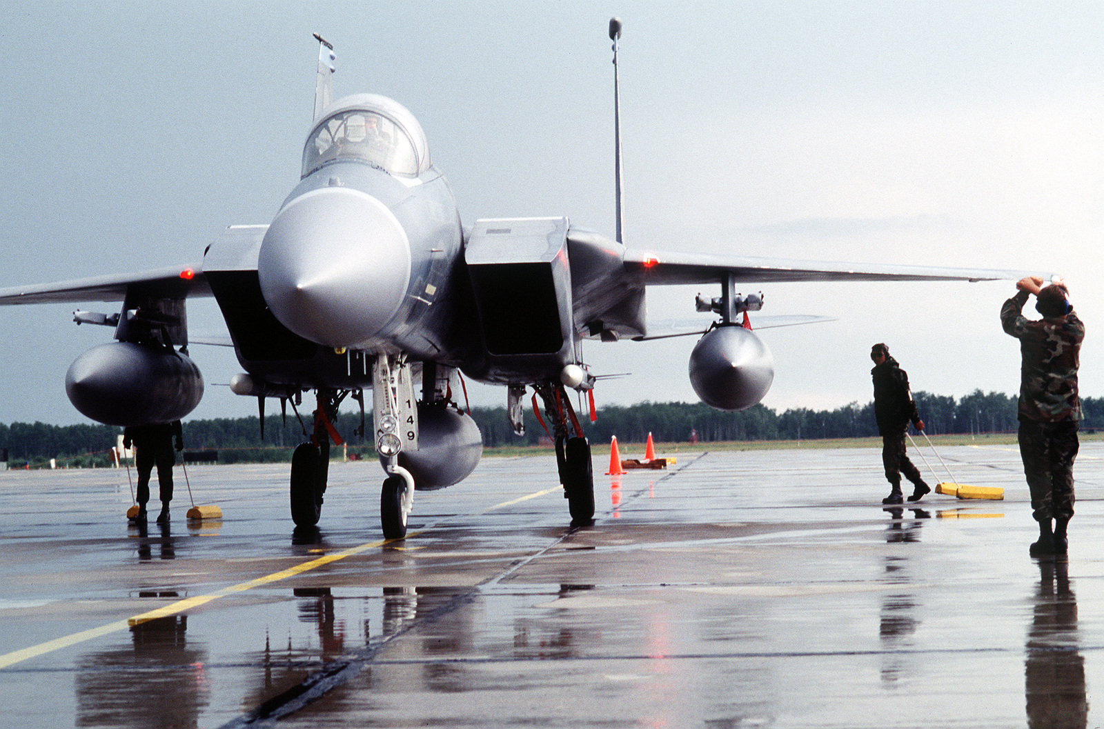 A member of the 390th Fighter Squadron, Mountain Home Air Force Base, Idaho marshals an F-15 Eagle to a stop on the flightline in a simulated wartime environment. Exact Date Shot Unknown