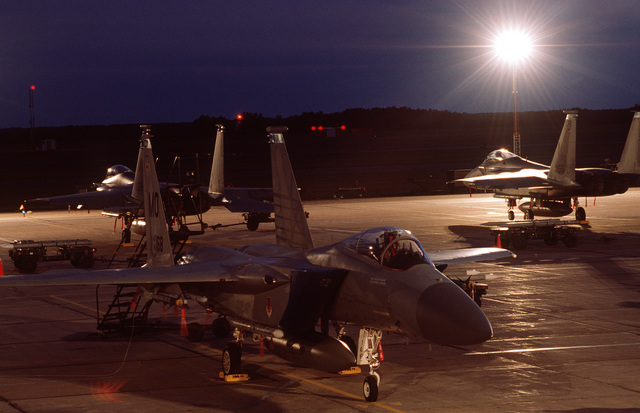 At night the F-15 Eagles from Mountain Home Air Force Base, Idaho sit on the illuminated flight line ramp awaiting tomorrow's operations. The F-15s are supporting an Operational Readiness Inspection (ORI), designed to test a unit's ability to operate in a simulated wartime environment. Exact Date Shot Unknown