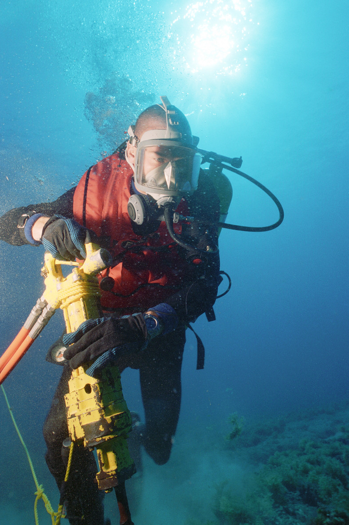 MASTER CHIEF (UCCM) Michael R. Oliver of Underwater Construction Team Two (UCT-2) drills holes in the coral bed next to the cable so that clamps can be placed for stabilization at the Pacific Missile Range Facility at Kauai, Hawaii