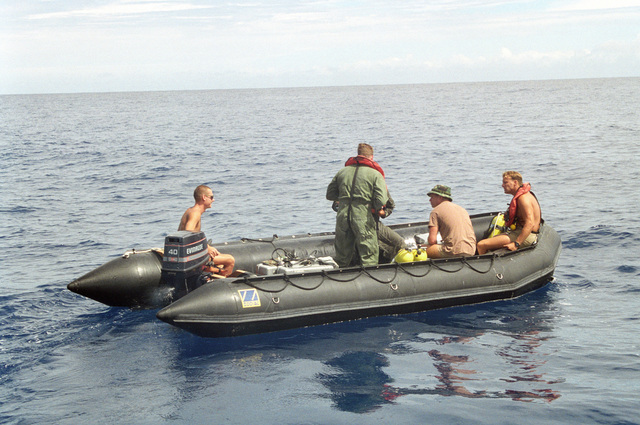 Members of Underwater Construction Team Two (UCT-2) and the Range Instruction Department from Point Magu, California are shown in a Zodiac boat while doing repair work on the Pacific Missile Range Facility off Kauai, Hawaii