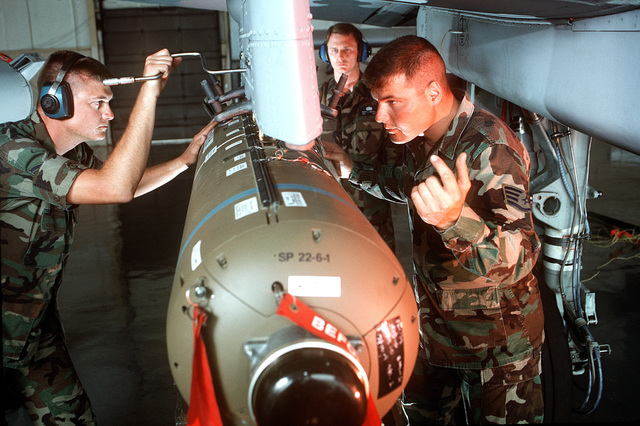"""USAF Sergeant Jason A. Barrigar (left) and STAFF Sergeant Ronald Sorrells, 347th Operations Group, Moody AFB, Georgia upload a CBU-87 (Cluster Bomb Unit) onto the wing pylon of and F-16 Falcon aircraft as STAFF Sergeant Rusty L. Harrell observes. From AIRMAN Magazine July 1995 issue """"Moody's on the Move"""""""