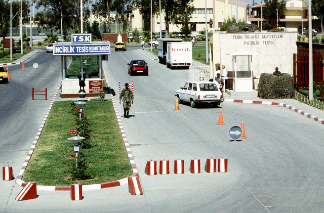 A long-range view of the main gate looking west. The gate is controlled and staffed by Turkish military. A U.S. Air Force Security Policeman serves on the gate as liaison