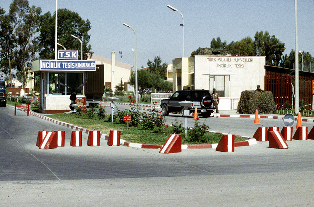 A medium-range view of the main gate looking west. The gate is controlled and staffed by Turkish military. A U.S. Air Force Security Policeman serves on the gate as liaison