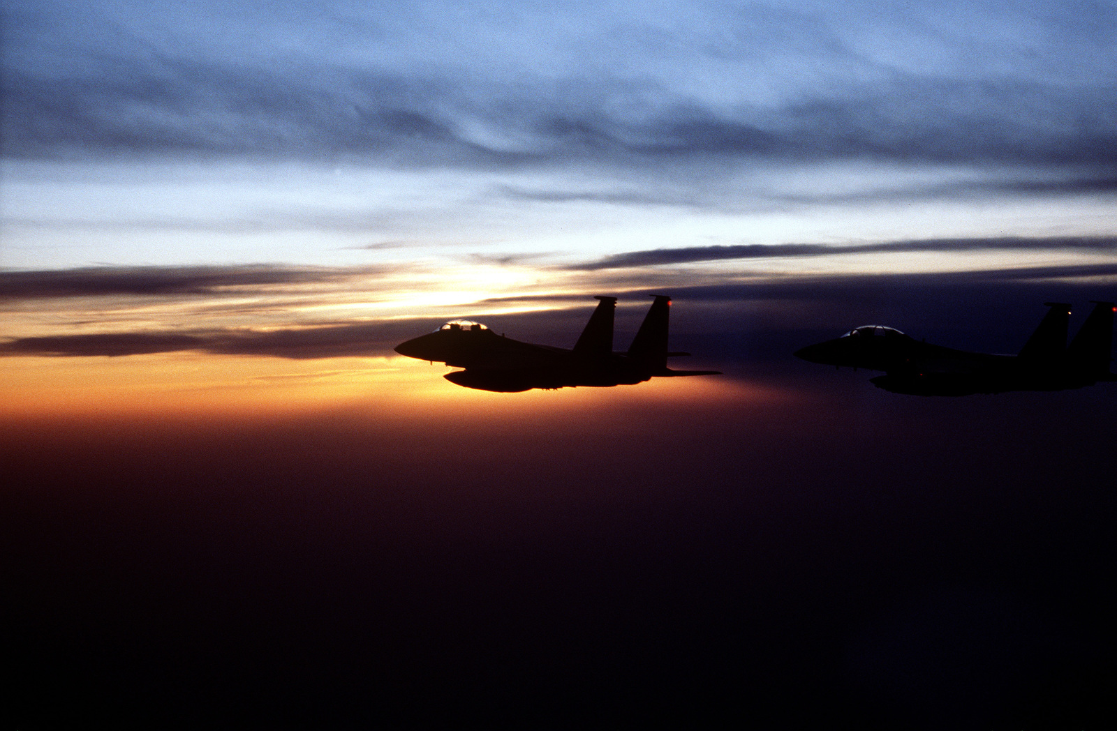 A silhouette of two US Air Force F-15E Strike Eagles from the 494th Fighter Squadron, Lakenheath Royal Air Force, England, in flight with sunset in background. The aircraft are flying sorties in support of the enforcement of a NATO no fly zone over Bosnia-Herzegovina