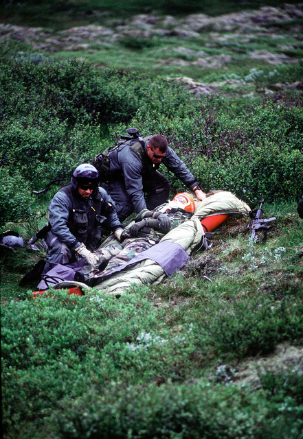 SSGT Mark Lerdall (without helmet) and SSGT Bill Peterson, Pararescuemen, 56th Rescue Squadron, Keflavik NAS, prepare an injured Marine for helicopter extraction from a simulated hostile area during NORTHERN VIKING '95. After the extraction the helicopter will fly the Marine to the hospital at Keflavik NAS. The simulation is part of NORTHERN VIKING '95, an exercise to test the plans of the defense of Iceland should the country ever be attacked