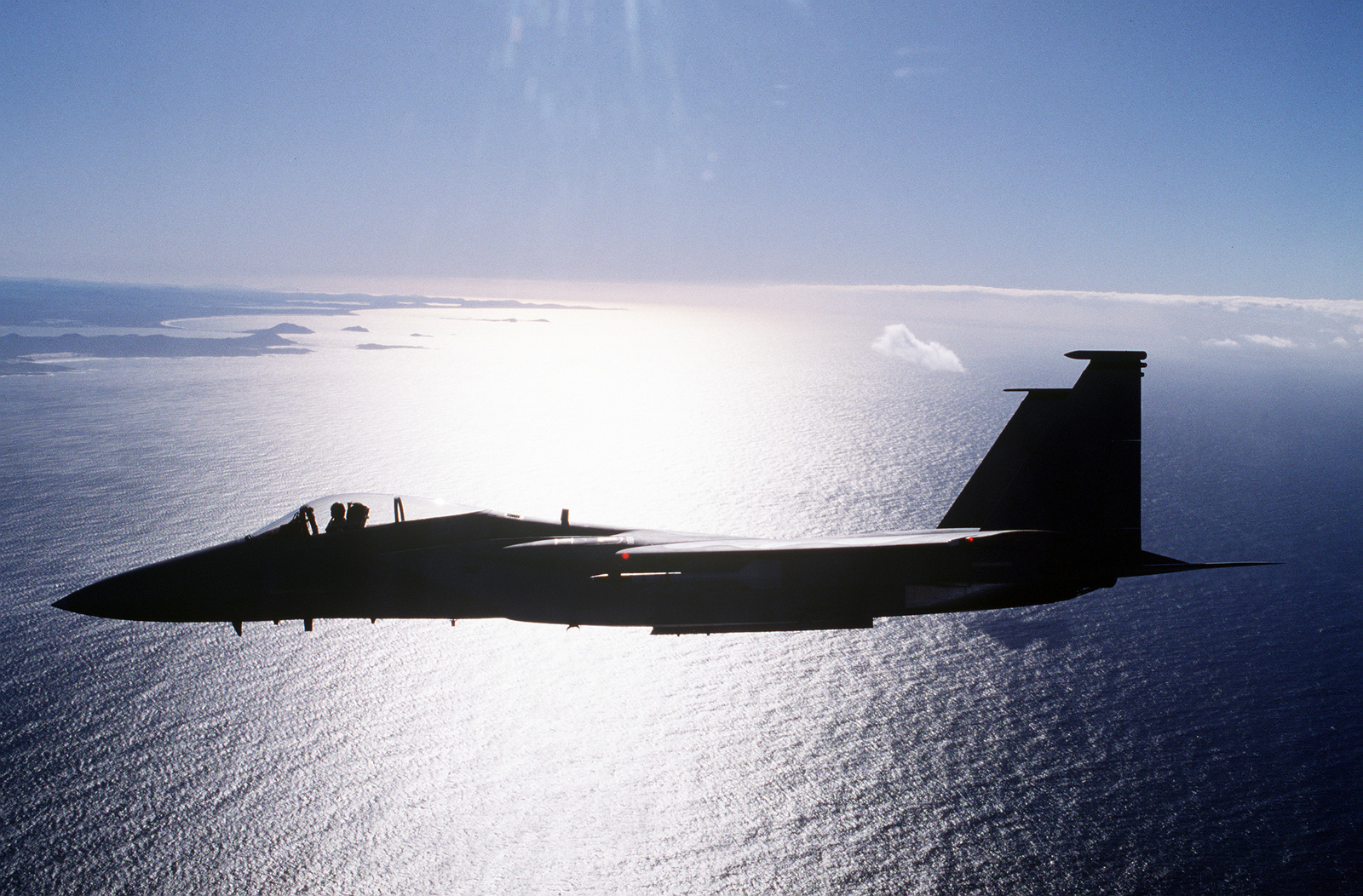 An aerial left side view of an F-15C silhouetted by the sun's reflection on the Indian Ocean. The aircraft, from the 44th Fighter Squadron, Kadena Air Base, Japan, patrols the air space around Williamtown during an air to air exercise between the United States Air Force and the Royal Australian Air Force