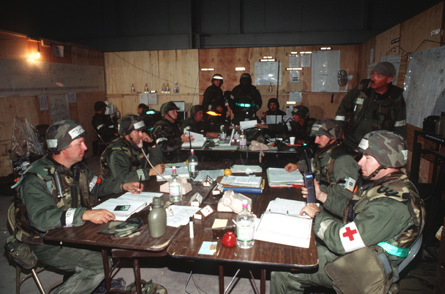 Deployed Wing Operations Center (WOC) personnel are comprised of representatives from many operational elements who keep the deployed commander informed. All are prepared to don Mission-Oriented Protective Posture response level 4 (MOPP-4) gear and MCU-2P gas masks at a moments notice. They are participating in the Operational Readiness Inspection (ORI), which tests a unit's ability to operate in a simulated wartime environment