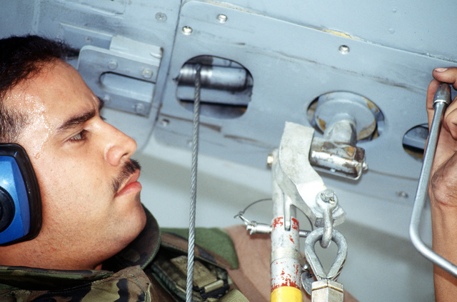 SGT Robert Ruiz, crew chief, 92nd Aircraft Generation Squadron (AGE), Fairchild Air Force Base, Washington sweats in the hot weather at Malmstrom Air Force Base, Montana. He is removing panel screws from a KC-135R Stratotanker to inspect the flying boom's winch mechanism during the Operational Readiness Inspection (ORI), which tests a unit's ability to operate in a simulated wartime environment