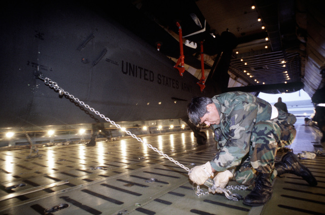 TSGT Edward Moinihan, 42nd Aerial Port Squadron, Westover Massachusetts, chains down a UH-60 Black hawk inside a C-5 Galaxy. The C-5 will transport equipment used in support of exercise NORTHERN VIKING '95 back to the United States