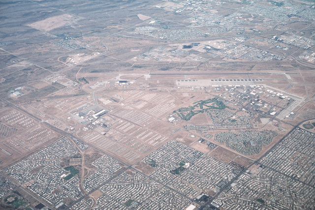 Low oblique aerial view looking southwest of the Air Force Base, home of Air Combat Command A-10A Thunderbolts and EC-130H Hercules aircraft of the 355th Wing. Adjacent to the complex is the Depart of Defense (DOD) Aerospace Maintenance and Regeneration Center (AMARC) storing surplus military and government aircraft no longer in service