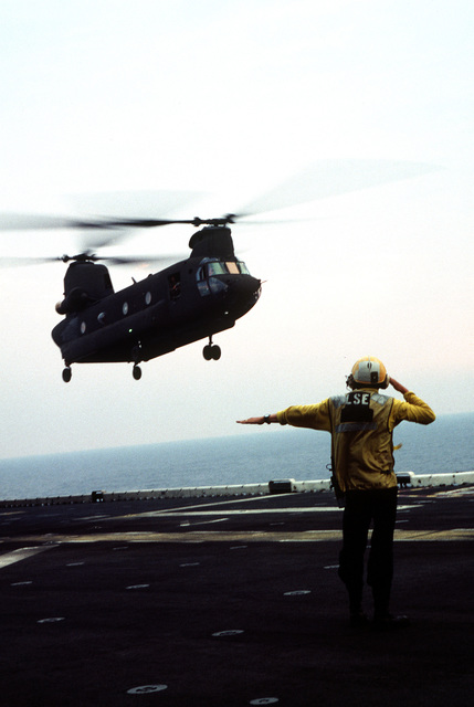 A flight deck crewman on the directs an US Army CH-47D Chinook helicopter to a spot on the flight deck during deck landing qualifications. The Army helicopter, from E Company, 502nd Aviation Regiment, Aviano, Italy, practices landings and take-offs from the deck of the amphibious assault ship as it operates off the coast of Italy
