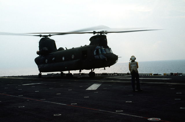A US Army CH-47D Chinook helicopter lands on the flight deck during deck landing qualifications. The Army helicopter, from E Company, 502nd Aviation Regiment, Aviano, Italy, practices landings and take-offs from the deck of the amphibious assault ship as it operates off the coast of Italy