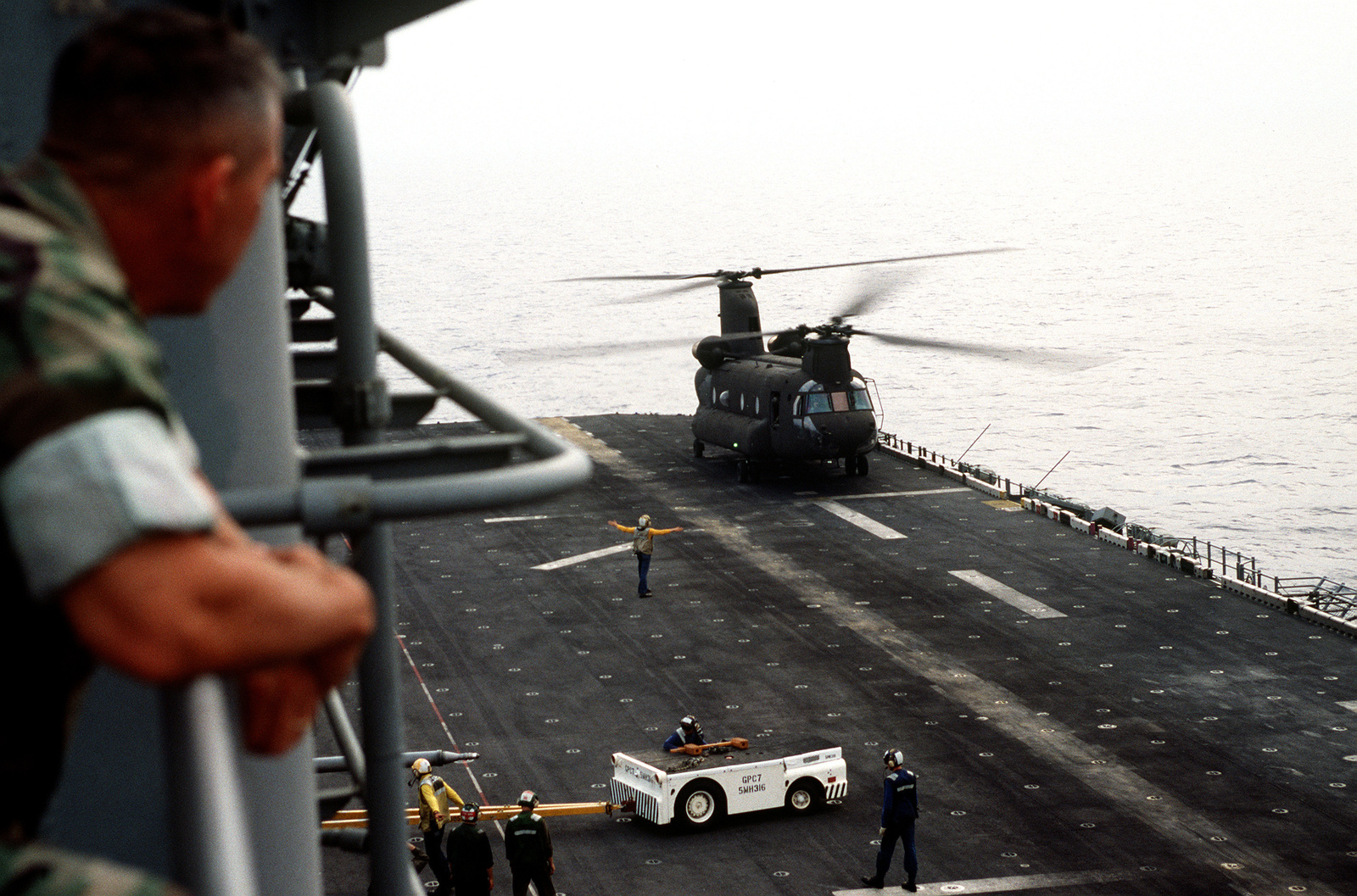 A US Army CH-47D Chinook helicopter lands on the flight deck for deck landing qualifications. The Army helicopter, from E Company, 502nd Aviation Regiment, Aviano, Italy, practices landings and take-offs from the deck of the amphibious assault ship as it operates off the coast of Italy