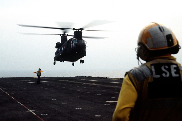 A US Army CH-47D Chinook helicopter makes an approach to the flight deck during deck landing qualifications. The Army helicopter from E Company, 502nd Aviation Regiment, Aviano, Italy, practices landings and take-offs from the deck of the amphibious assault ship as it operates off the coast of Italy