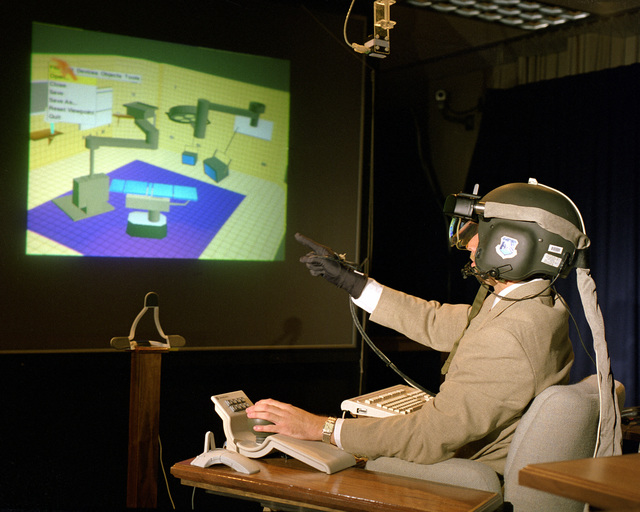 A virtual reality system in use. The 3-D helmet controls a large image screen with voice and glove interfacing to the computer system. The system, currently in use at Rome Laboratory could be used in conjunction with other application programs to highlight special interest targets as in the case of mobile or intel targets. The glove and voice inputs provide natural and simpler user interface to the computer in a graphical mode. The helmet allows the user to preview specific information or highlight a subset or the screen image prior to inclusion for the audience. The helmet was joint development effort with Rome Laboratory, Armstrong Laboratory, and Wright Laboratory. The software is ...