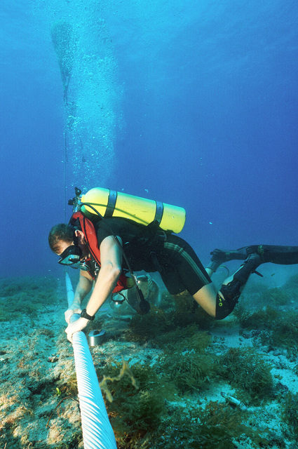 CHIEF Equipment Operator (EOC) Robert Duran places cable wraps on a section of damaged underwater cable at the Pacific Missile Range Facility off Kauai, Hawaii.(Exact date unknown)