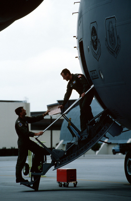 "US Air Force First Lieutenant Brian Langridge and Captain Pat Tibbetts Brian Langridge and Captain Pat Tibbetts discuss the aircraft flight plans, standing on the crew door steps of a C-17A Globemaster III aircraft, from the 437th and 315th Airlift Wing, Charleston Air Force Base, South Carolina. From AIRMAN Magazine October 1995 article ""Redemption"""
