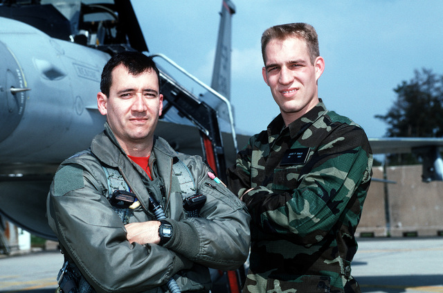 """USAF Captain (CPT) Tom Smith (left), a F-16 Falcon aircraft pilot assigned to the 22nd Fighter Squadron, Spangdahlem Air Base, Germany and USAF SENIOR AIRMAN (SRA) Jason Fowler a aircraft armament systems specialists, 22nd Fighter Squadron pose for a photograph on the flight line at Spangdahlem AB, Germany. CPT Smith and SRA Fowler both were forced to eject from the F-16 Falcon aircraft in which they were flying when the aircraft's engine failed. From AIRMAN Magazine's August 1995 issue article """"Friday the 13th: The Horror Continues-Jason Jettisoned"""""""