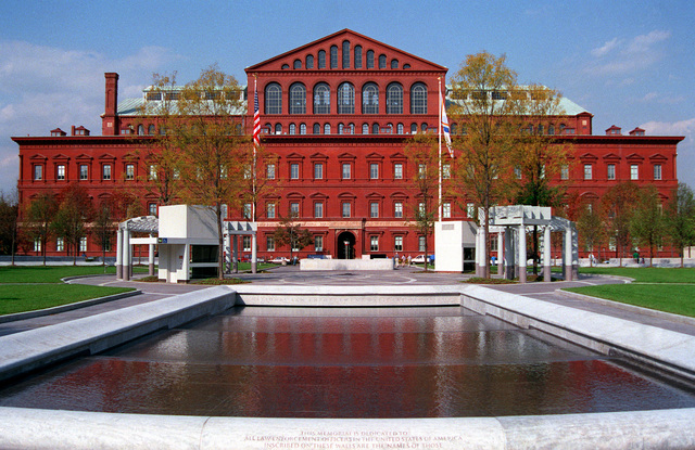 A view of the fountain in the center of the National Law Enforcement Officer's Memorial. Inscribed on its surrounding walls are the names of all law enforcement officers who gave their lives in the line of duty. In the background is the old Pension Building, now the National Museum Building