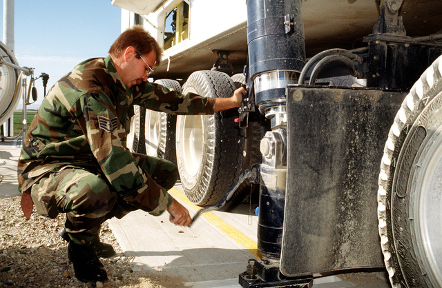 After the transporter/erector vehicle at the Launch Facility is backed up to K-11's massive launch tube door and bolted to mounts at the edge of the opening, STAFF SGT. Johnnie Wheeler, 341 MXS, turns a handcrank on one of the hydraulic jacks under the vehicle. The jacks are used to make the vehicle level, stabilize it during operation, and adjust the angle that the missile is hoisted up into the transporter/erector