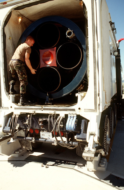 An airman standing in the rear of the transporter/erector vehicle, makes the final adjustment to the Air Force's last Minuteman II intercontinental ballistic missile to be deactivated. The missile will eventually join other retired Minuteman II's at a depot at Hill AFB, Utah