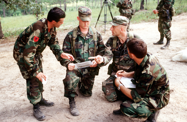 CAPT. James Skidmore (second from left), an observer/trainer with the US Army, briefs Albanian Army platoon leaders on land mine detection in a Situational Training Exercise. Soldiers from three NATO and 14 other central and eastern European countries are developing their combined peacekeeping skills during the exercise at the Joint Readiness Training Center. Cooperative Nugget '95 is the sixth Partnership for Peace exercise, but the first to be held on US territory