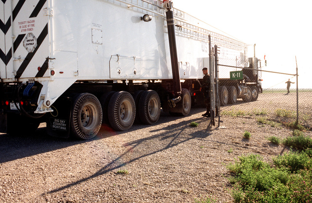 "In the morning around 0800 at the Launch Facility, security policeman SENIOR AIRMAN Blake Wingate of 341 OSS holds open Launch Facility K-11's gate and allows a transporter/erector vehicle from the 341 Missile Maintenance Squadron to come onto the site. Today the truck will be removing the 341 Missile Wing's last Minuteman II intercontinental ballistic missile from its launcher, marking the end of thirty years of Minuteman II's in the Air Force inventory and the completion of President Bush's 1991 ""Stand Down"" order which removed all Minuteman II missiles from alert"