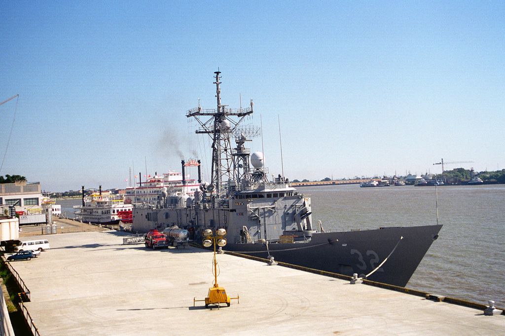 A starboard bow view of the guided missile frigate USS JOHN L. HALL (FFG-32) tied up at a municipal pier during a port visit