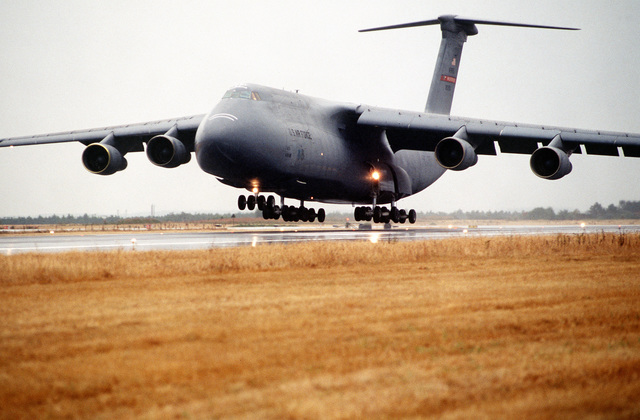 A C-5 Galaxy lands at Karup Air Station. The plane is loaded with equipment and personnel from the 52nd Tactical Fighter Wing, Spangdahlem AB, Germany. The 52nd TFW is deployed to Karup to participate in a three week exercise designed to test the effectiveness of both the American and Danish air defenses. Exact Date Shot Unknown