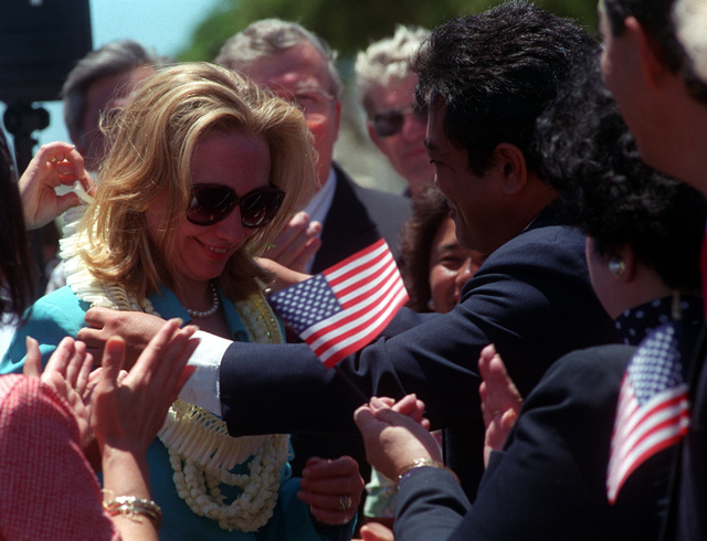 A close up view of First Lady Hillary Clinton as she is greeted on her arrival by the crowd waving United States flags. She is here for the commemoration of the 50th anniversary of World War II