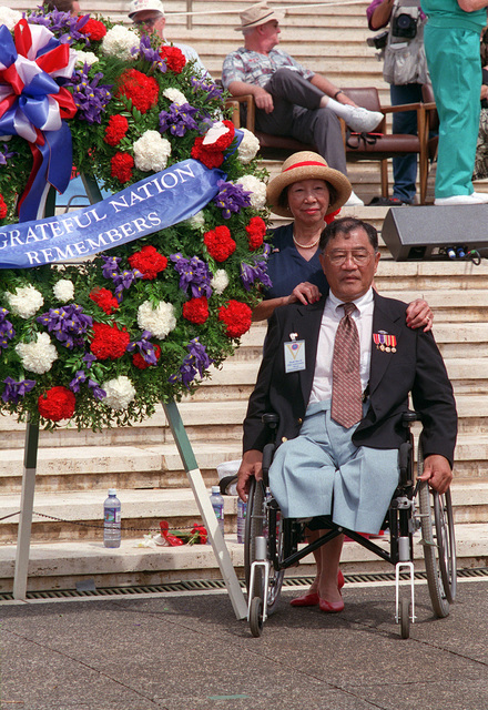 A decorated Hawaiian war veteran poses with his wife beside the large wreath he presented at Punchbowl National Cemetery of the Pacific during the ceremony commemorating the 50th anniversary of the end of World War II
