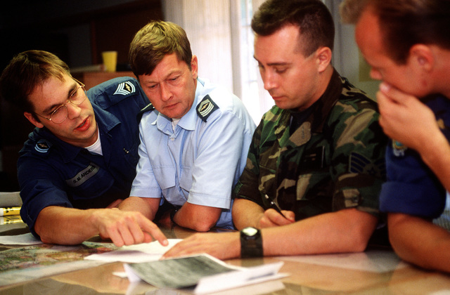 STAFF SGT. Gary P. Lindmark, 22nd Fighter Squadron, 53rd Fighter Wing, Spangdahlem AB, Germany, discusses range scores with Target Intelligence Specialists from the Royal Danish Air Force. Exact Date Shot Unknown