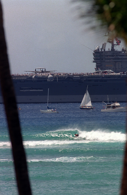 The nuclear powered carrier, USS CARL VINSON (CVN-70), leaves Pearl Harbor during the parade of ships and planes commemorating the 50th anniversary of World War II. Small craft and a surfer can be seen in the foreground