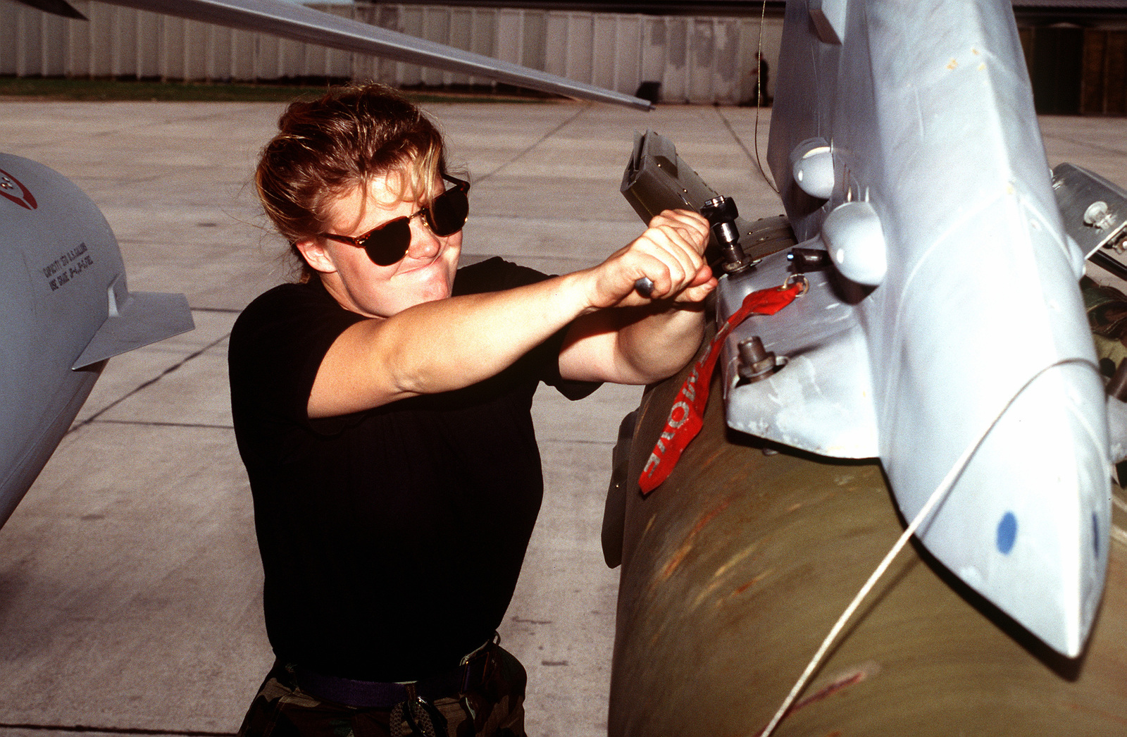 A female weapons loader load GBU-10 munitions onto a US Air Force F-16C Fighting Falcon aircraft from the 555th Fighter Squadron in preparation for NATO airstrikes against the Bosnian Serbs