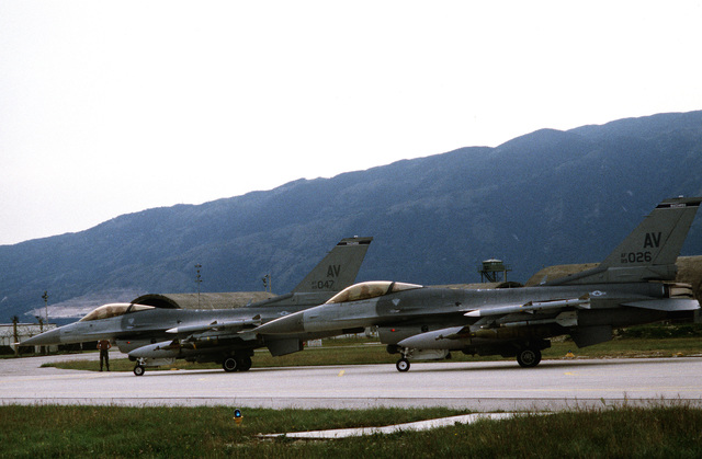 A medium shot of two US Air Force F-16C Fighting Falcons as they taxi on the runway for take off for NATO airstrikes against the Bosnian Serbs