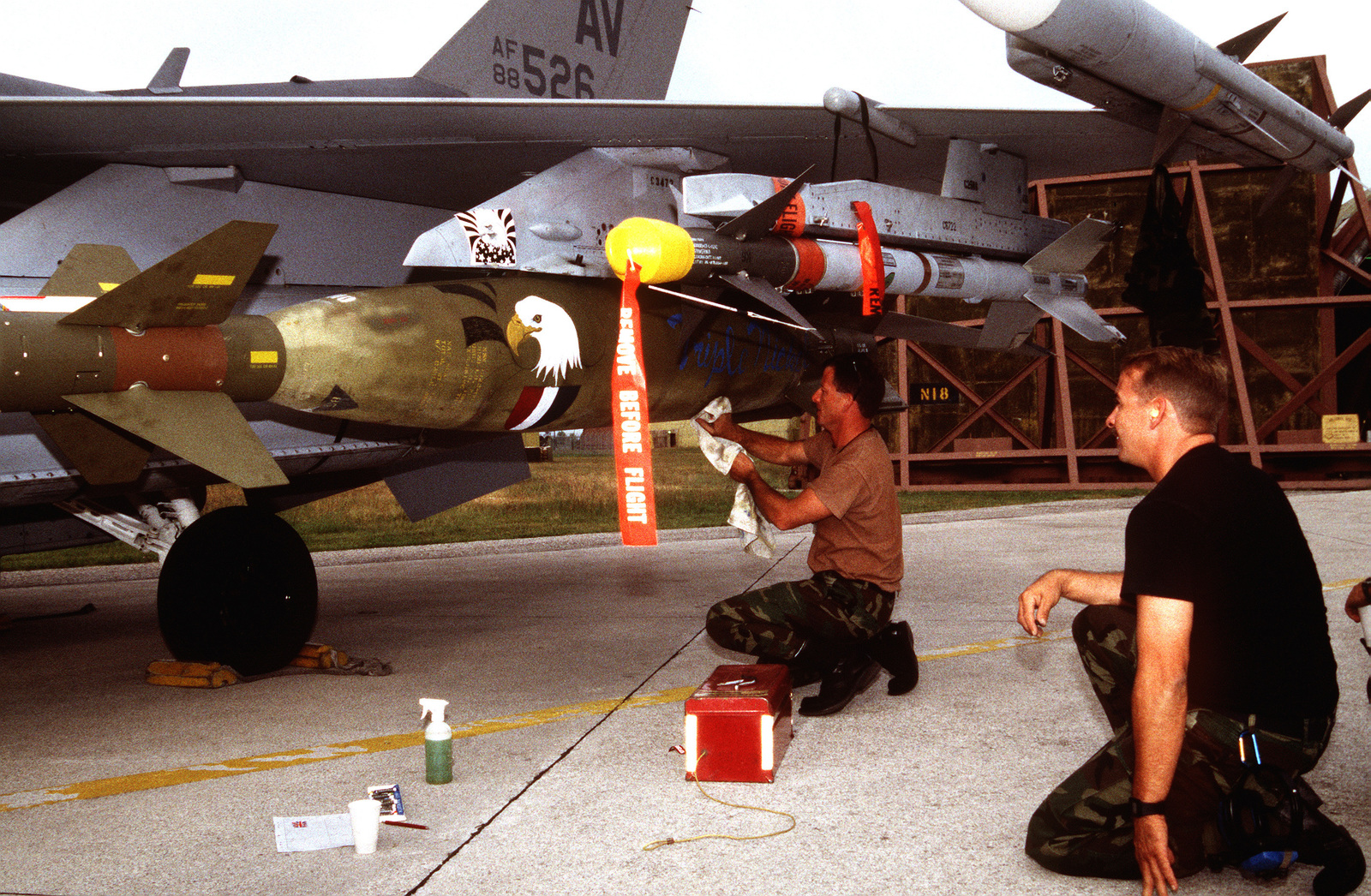 US Air Force STAFF Sgts. Day (left) and Barr (right), of the 555th Fighter Squadron, paint the Triple Nickel logo onto the munitions of a F-16C Fighting Falcon being prepared for NATO airstrikes against the Bosnian Serbs. A sidewinder missile is mounted above SGT. Days head on the wing pylon