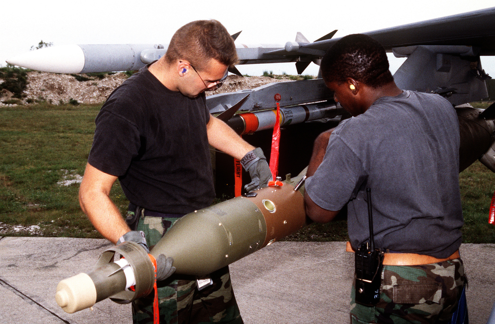 Weapon loaders load a HARM or High-speed Anti-Radiation Missile onto a US Air Force F-16C Fighting Falcon aircraft from the 555th Fighter Squadron in preparation for NATO airstrikes against the Bosnian Serbs