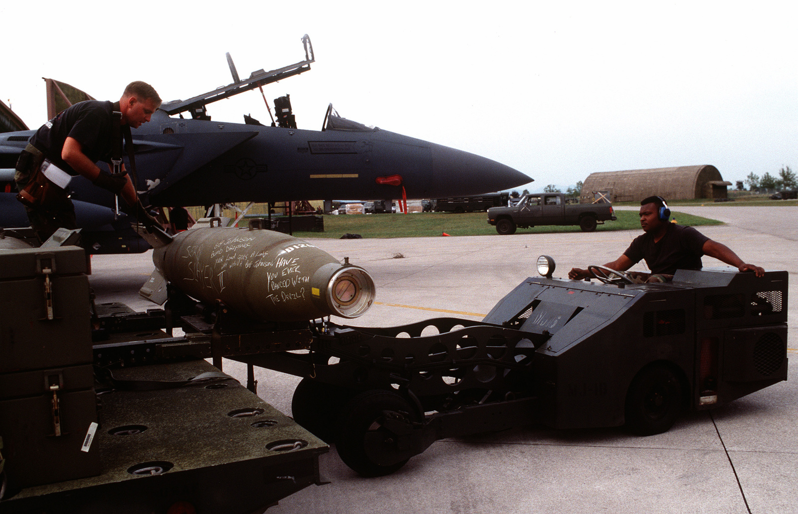 Weapon loaders offload the main body warhead and tail section of a laser guided bomb from a heavy expanded mobility ammunitions trailer prior to being loaded onto a US Air Force F-16C Fighting Falcon aircraft from the 555th Fighter Squadron for NATO airstrikes against the Bosnian Serbs. An F-15 is parked in the background