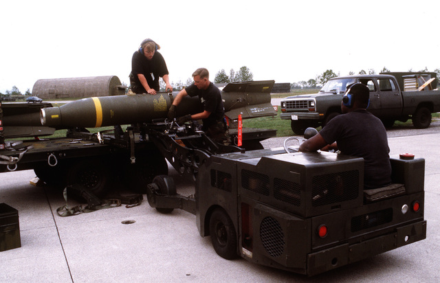 Weapon loaders prepare the main body warhead and tail section of a laser guided bomb prior to being loaded onto aircraft for NATO airstrikes against the Bosnian Serbs