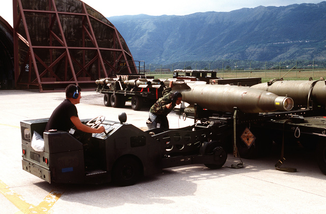 Weapon loaders unload GBU-10 munitions from an M989A1 heavy expanded mobility ammunition trailer (HEMAT) in preparation for NATO airstrikes against the Bosnian Serbs