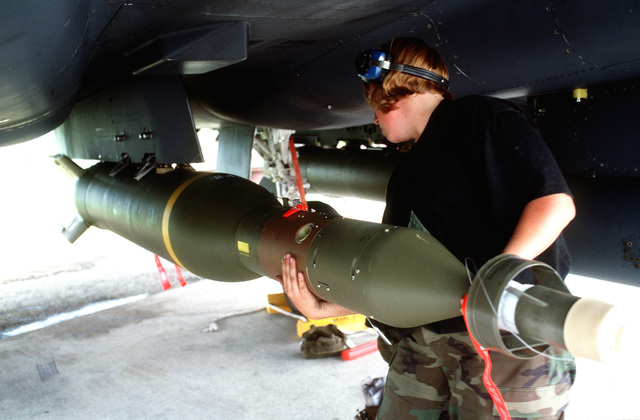 Weapons loaders from the 555th Fighter Squadron load a laser guided bomb system onto a US Air Force F-15 Eagle from the 494th Fighter Squadron, Royal Air Force Lakenheath, England, for NATO airstrikes against the Bosnian Serbs