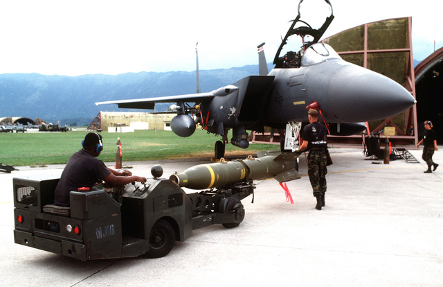 Weapons loaders prepare the main body warhead and tail section of a laser guided bomb for loading onto a US Air Force F-15 Eagle from the 494th Fighter Squadron, Royal Air Force Lakenheath, England, for NATO airstrikes against the Bosnian Serbs. The weapon loaders are from the 555th Fighter Squadron