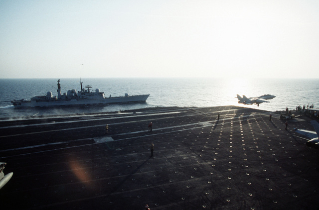 An F-14 Tomcat aircraft of Fighter Squadron 154 (VF-154) is launched from waist catapult four on board the aircraft USS Independence (CV-62) just after sunrise in the Persian Gulf. Steaming alongside the Indy is the United Kingdom Royal Navy guided missile destroyer HMS Gloucester (D-96)