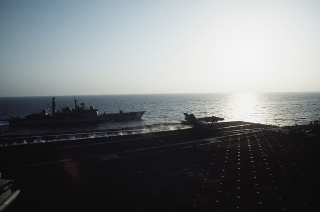 An F/A-18 Hornet aircraft of Strike Fighter Squadron 195 (VFA-195) is catapulted from the waist position on board the aircraft carrier USS Independence (CV-62) into the early morning sunrise of the Persian Gulf. The United Kingdom Royal Navy guided missile destroyer HMS Gloucester (D-96) is steaming close aboard the port side of the Indy